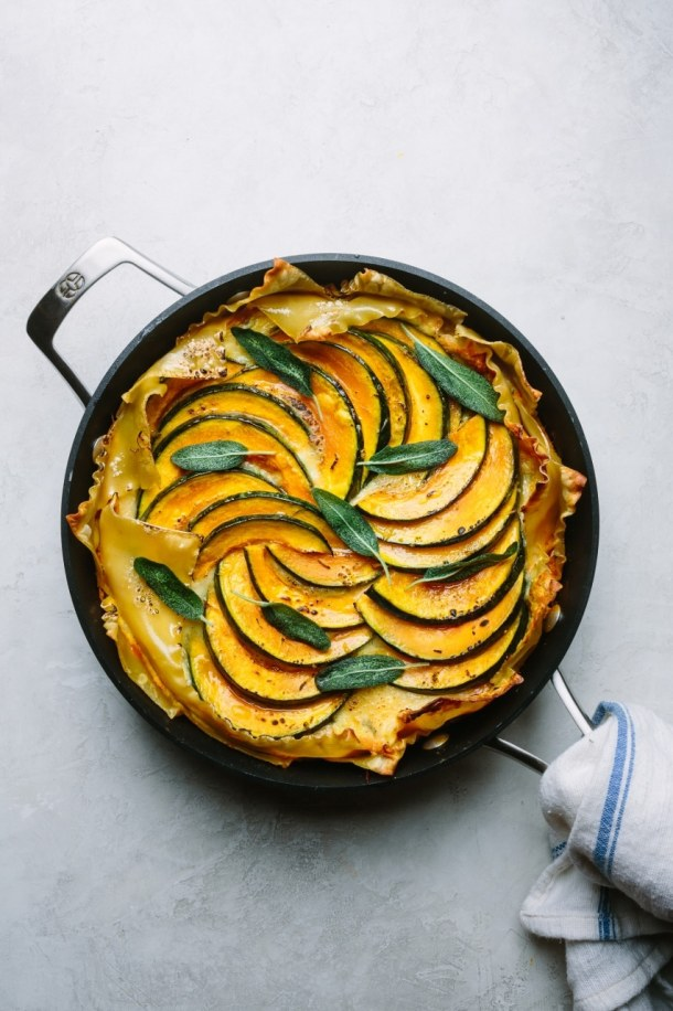 a skillet of baked pumpkin ricotta lasagna with a napkin wrapping around the handle