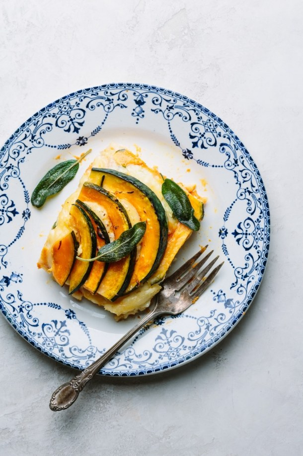 a blue plate with a slice of baked pumpkin ricotta lasagna and a fork