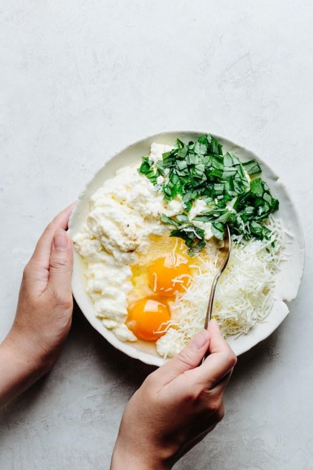hand stirring a bowl containing ricotta cheese, mozzarella cheese, 2 eggs, chopped basil