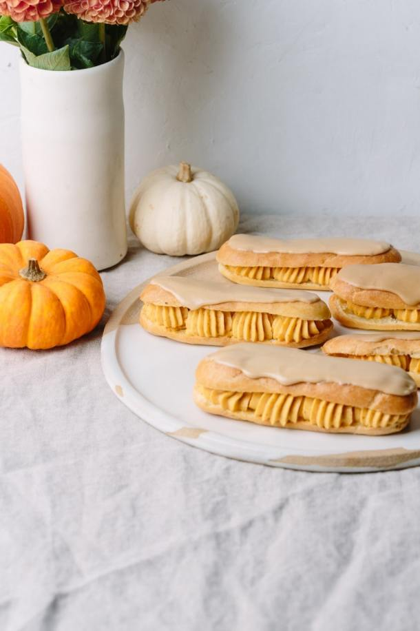 a plate of salted caramel pumpkin eclairs with mini pumpkins and a vas of flowers