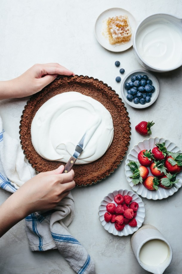 hand spreading yogurt over crust with spatula next to a kitchen towel, a plate of raspberries, a plate of strawberries, a bowl of blueberries, a bowl of yogurt, and a plate with honeycomb, and creamer