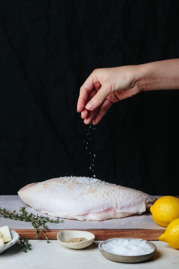 hand seasoning turkey breast with salt, next to lemons, bowl of salt, pepper, butter, and thyme