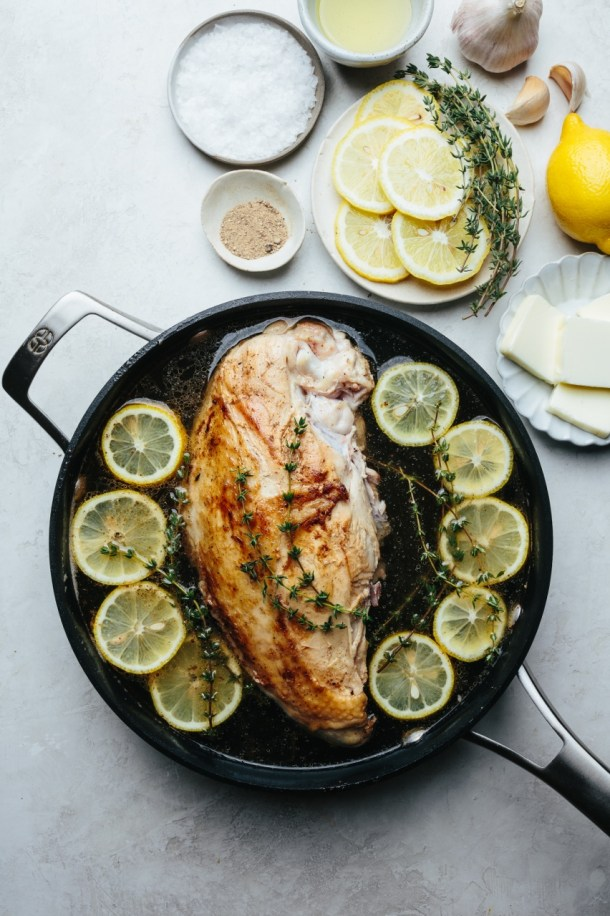 poached turkey breast in pan next to bowl of salt, pepper, olive oil, plate of lemon slices with thyme, plate of butter, garlic cloves, and fresh lemon