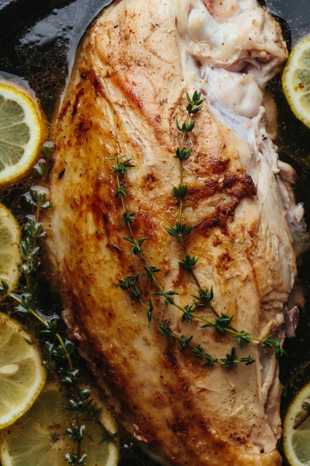 poached turkey in pan with broth, lemon slices, and thyme