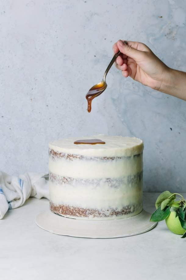 hand holding spoon dripping salted caramel on the frosted toffee apple cake next to a green apple and kitchen towel