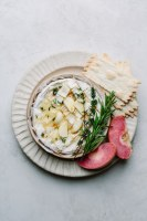 baked Camembert with garlic and herbs on plate served with apple and crackers