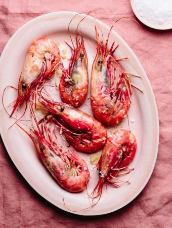 a plate of gambas a la plancha with a small plate of sea salt
