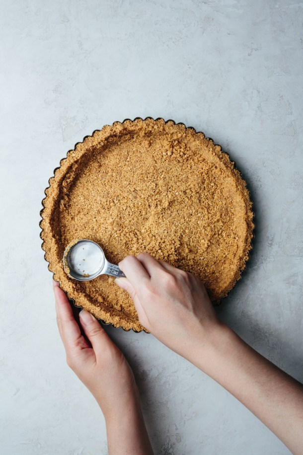 a hand pressing the Graham cracker crumb mixture into the tart pan while another hand is holding the pan