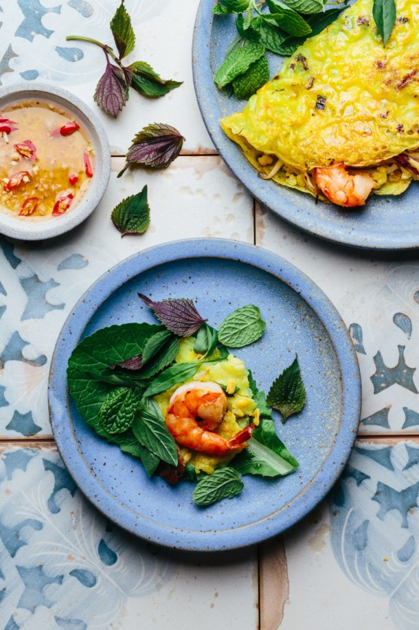a plate with Vietnamese crepe and fresh herbs next to a bowl of dipping sauce and a plate with mustard green topped with a piece of crepe, prawn, and fresh herbs ready to be rolled up