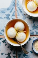 two bowls with glutinous rice balls in ginger syrup and a small plate of sesame seeds