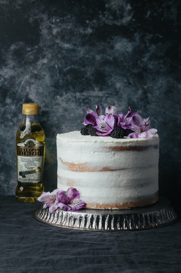 blackberry Earl Grey cake on a metal stand next to an olive oil bottle