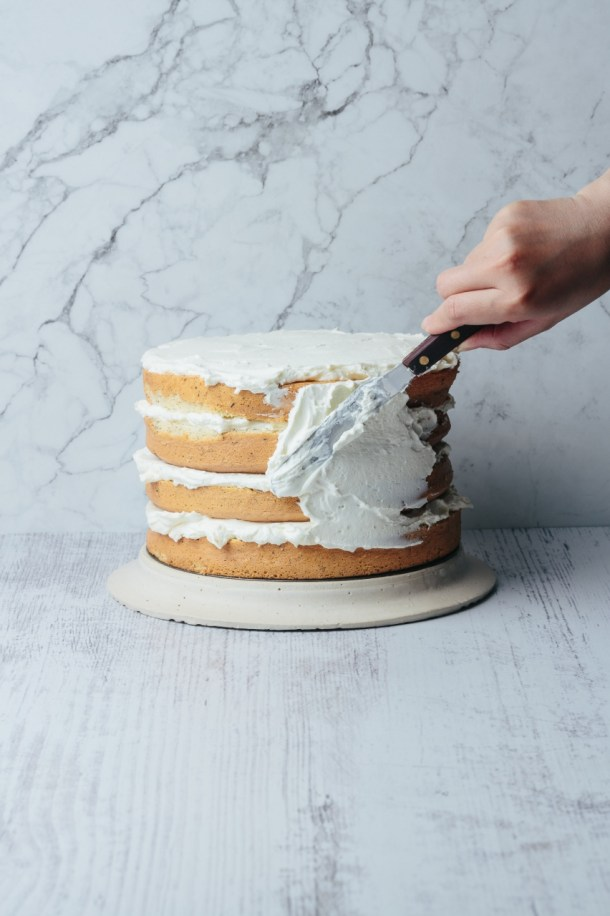 hand frosting 4 layered cake with spatula