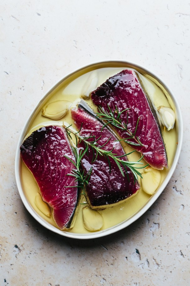 raw tuna in a baking dish with olive oil, garlic, and fresh rosemary