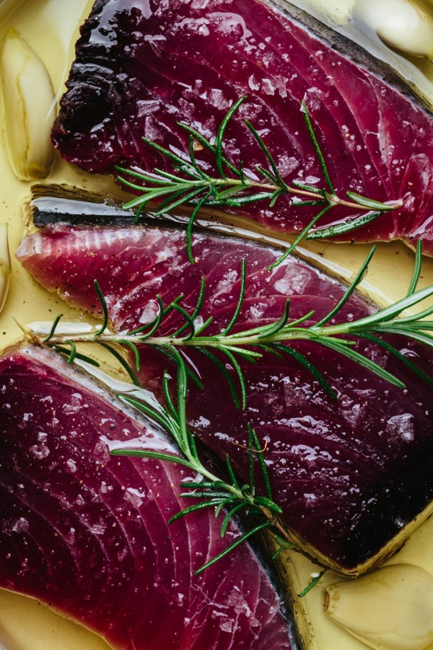 close up of raw tuna in a baking dish with olive oil, garlic, and fresh rosemary