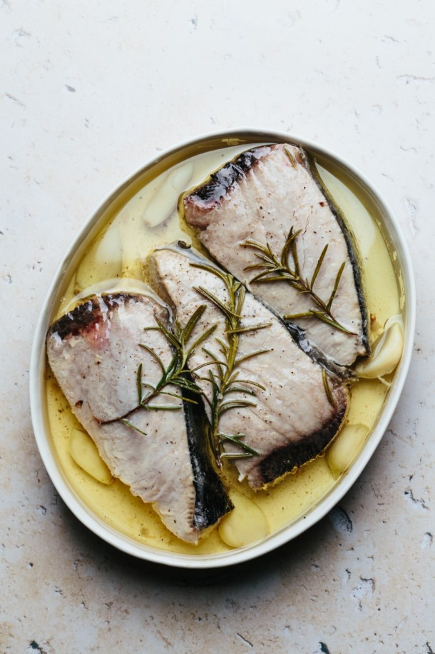 tuna confit in a baking dish with olive oil, garlic, and rosemary