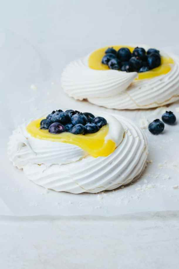 two baked Swiss meringue pavlova nests on a white parchment paper