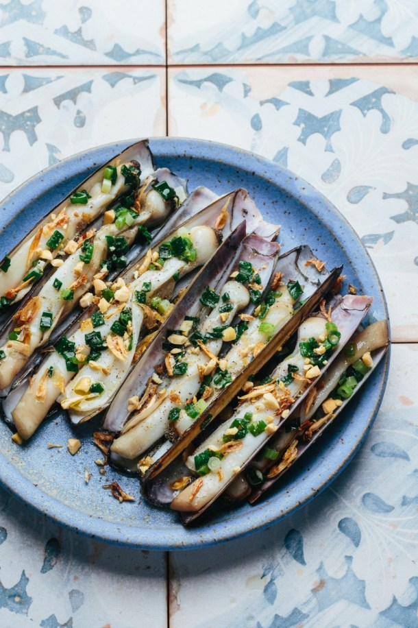 a plate of grilled razor clams topped with scallion oil, fried shallots, and roasted peanuts