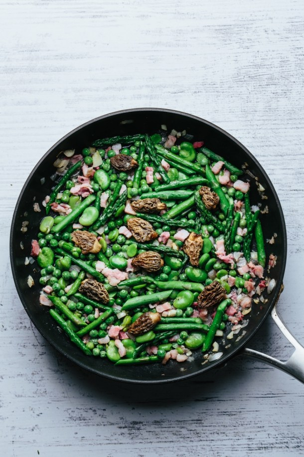 a pan with cooked fava, peas, asparagus, morel, and pancetta