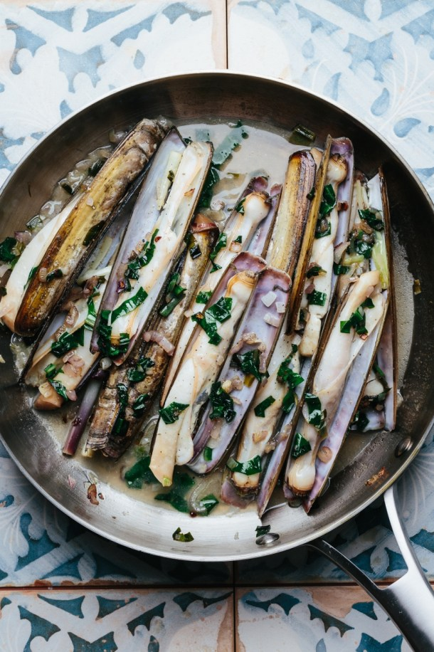 a pan of steamed razor clams with ramps and white wine
