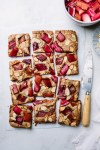 baked rhubarb white chocolate blondies cut into 12 squares next to a knife, bowl of rhubarb, and plate of almods