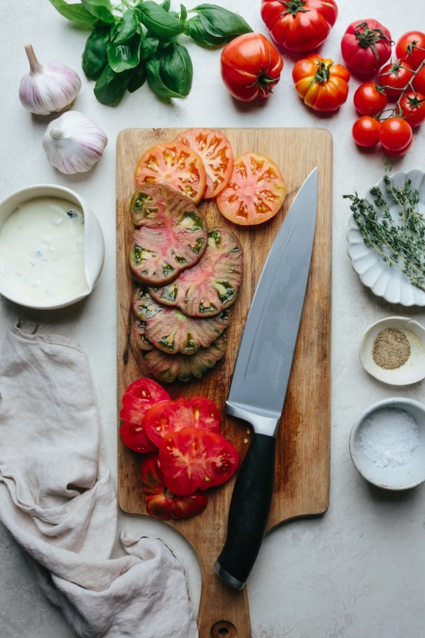 sliced tomatoes on a chopping board next to a knife, next to fresh tomatoes, basil leaves, 2 heads of garlic, and a bowl of ricotta filling, a plate of thyme leaves, a bowl of salt, and a bowl of pepper