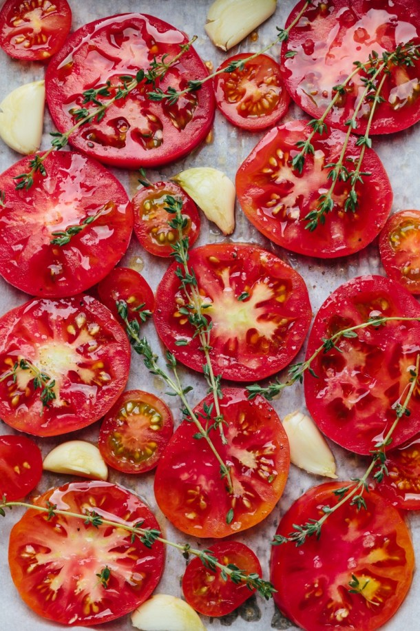 a close up of tomato slices, garlic cloves, and thyme for roasting