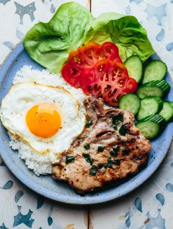 a plate of broken rice with grilled lemongrass pork chop, a fried egg, lettuce, tomatoes, and cucumber