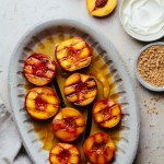 a bowl with grilled peaches in syrup next to a kitchen linen, a bowl of whipped mascarpone, a bowl of amaretti cookies, and fresh peaches
