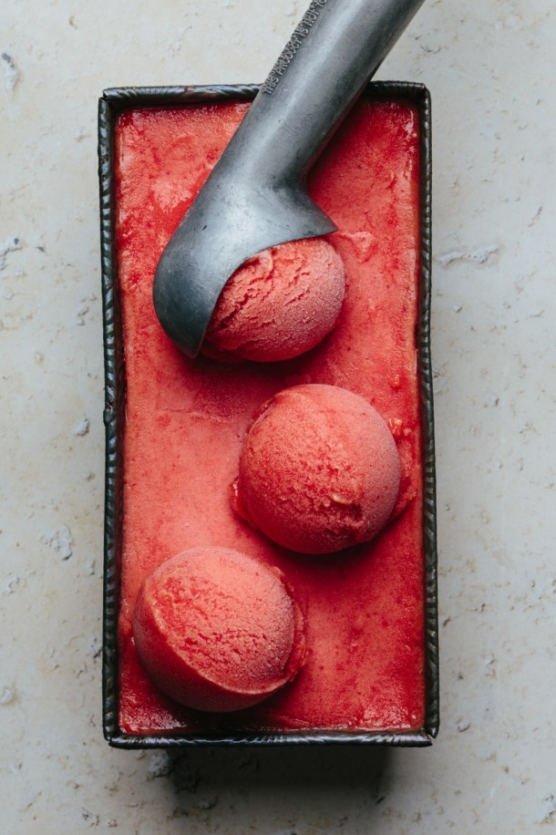 a container with three scoops of hibiscus peach sorbet and ice cream scoop