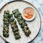 a plate with three skewers of grilled beef wrapped in betel leaves topped with peanuts next to a bowl of dipping sauce