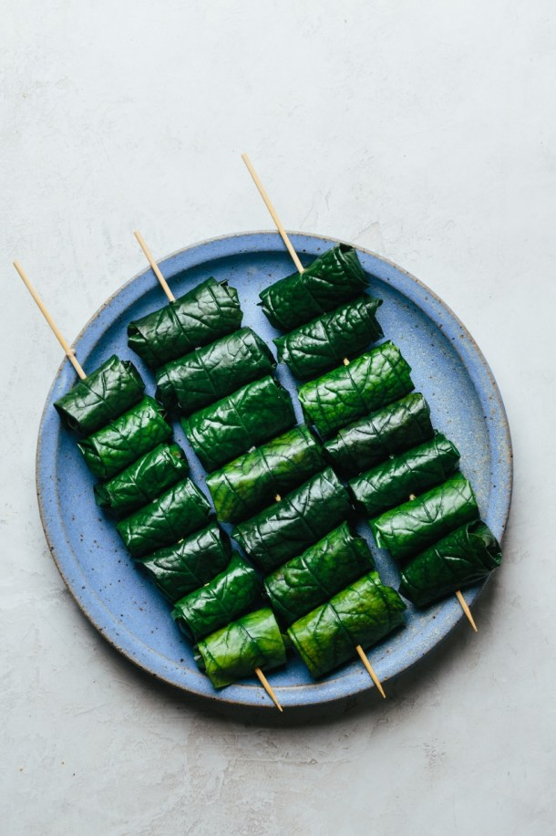 a plate with three skewers of beef wrapped in betel leaves