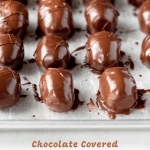 Angled image of just dipped chocolate covered peanut butter eggs on a baking sheet | © Beyond the Butter, LLC