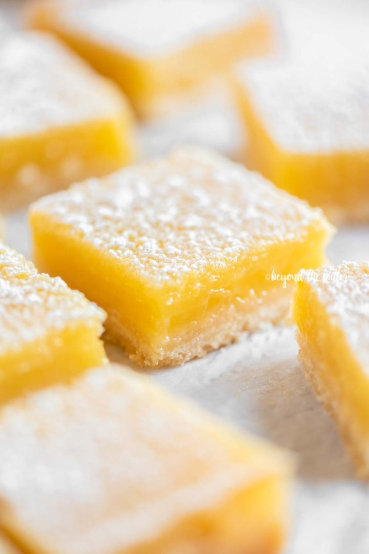 Angled image of super easy lemon bars dusted with confectioners sugar | All Images © Beyond the Butter, LLC