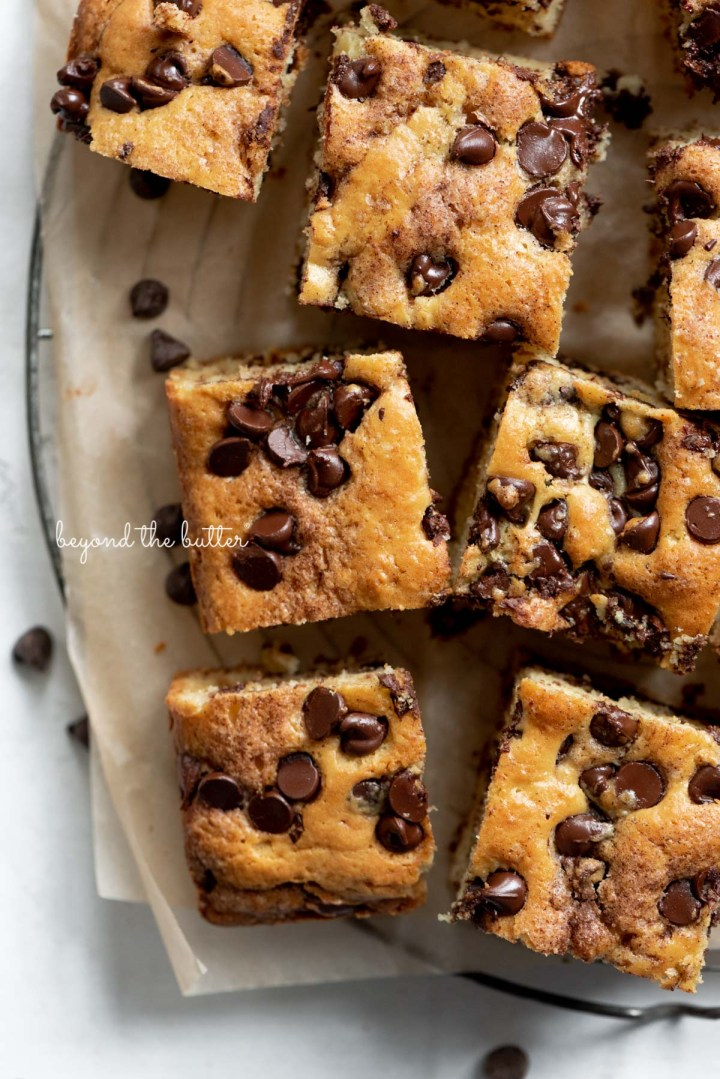 Chocolate chip sour cream coffee cake on brown parchment paper lined wire cooling rack | © Beyond the Butter®