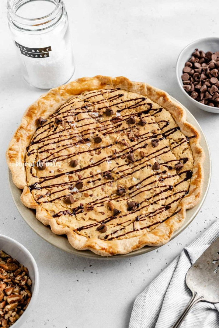 Overhead angled image of chocolate chip pie drizzled with chocolate syrup with bowls of chocolate chips, pecans, and a server | All Images © Beyond the Butter™