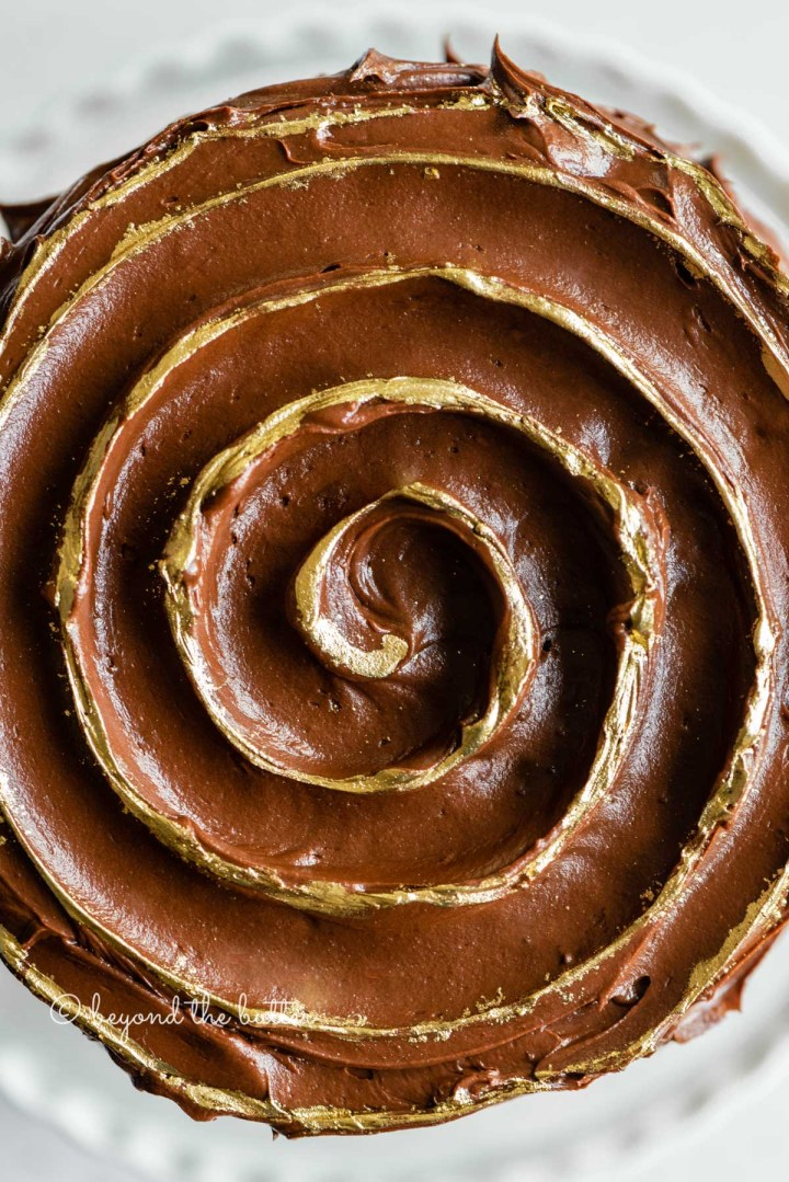Overhead closeup image of chocolate zucchini cake with chocolate chips and gold decorative swirl on top | All Images © Beyond the Butter™