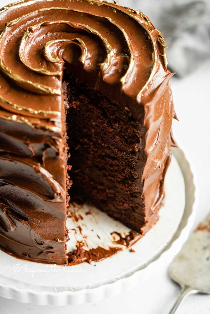 Angled closeup image of chocolate zucchini cake with gold decorative swirl on top and slice removed | All Images © Beyond the Butter™