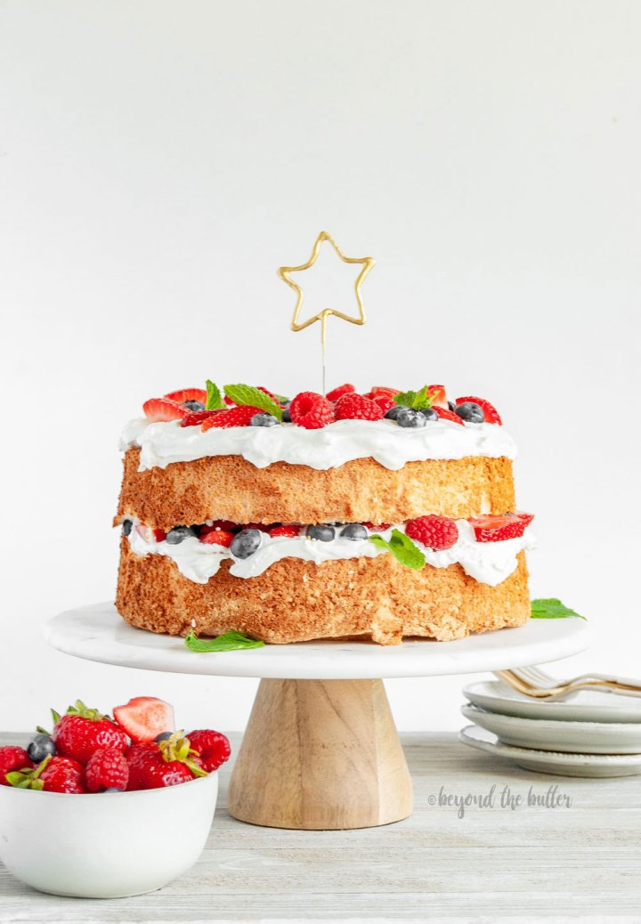 Angel Food Cake with Berries | Angel Food Cake on a cake stand | Image and Copyright Policy: © Beyond the Butter, LLC