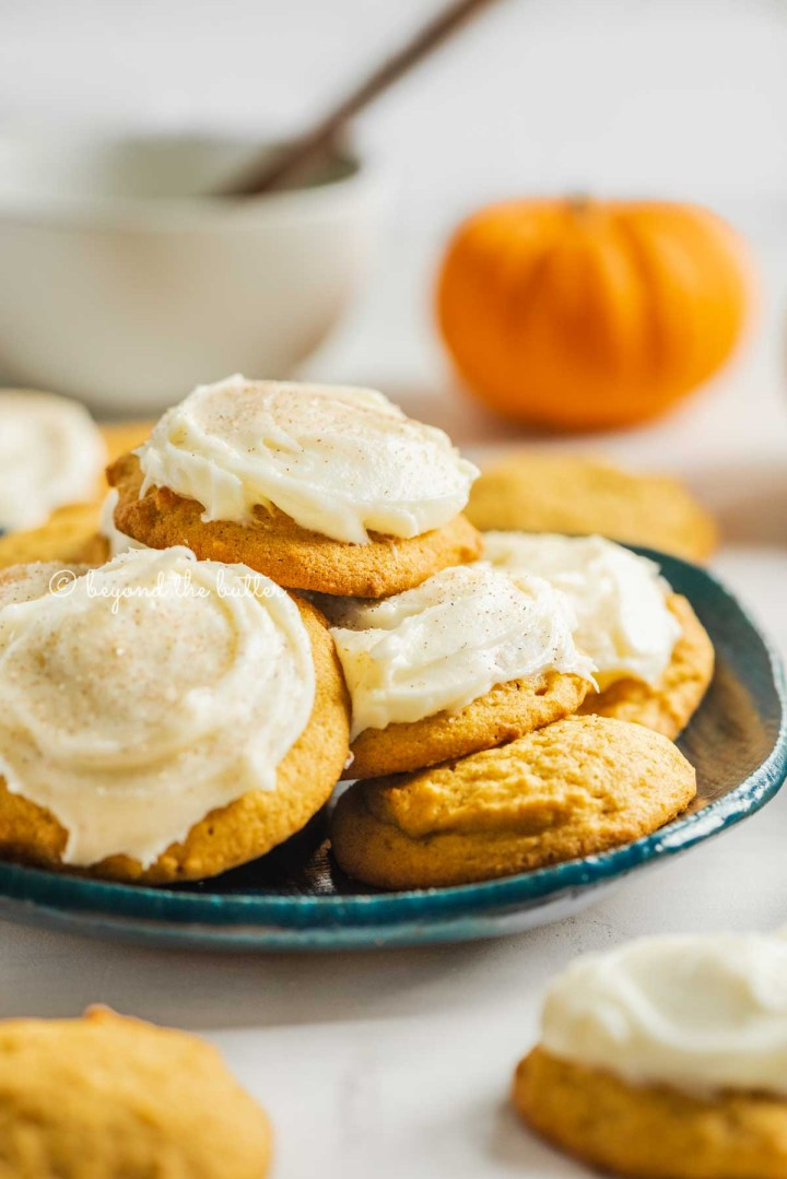 Pumpkin cinnamon cookies topped with cream cheese frosting served on plate with more cookies and pumpkin in the background | All Images © Beyond the Butter™