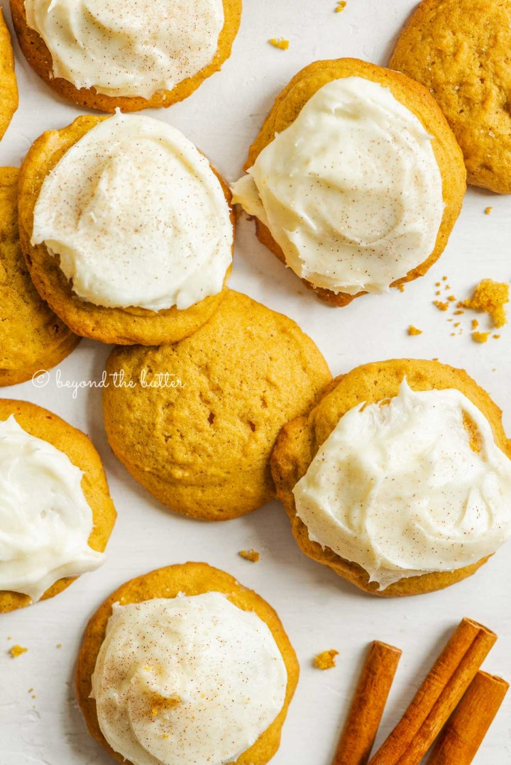 Plain and cream cheese frosted pumpkin cinnamon cookies with cinnamon sticks randomly place bottom right on a white background | All Images © Beyond the Butter™