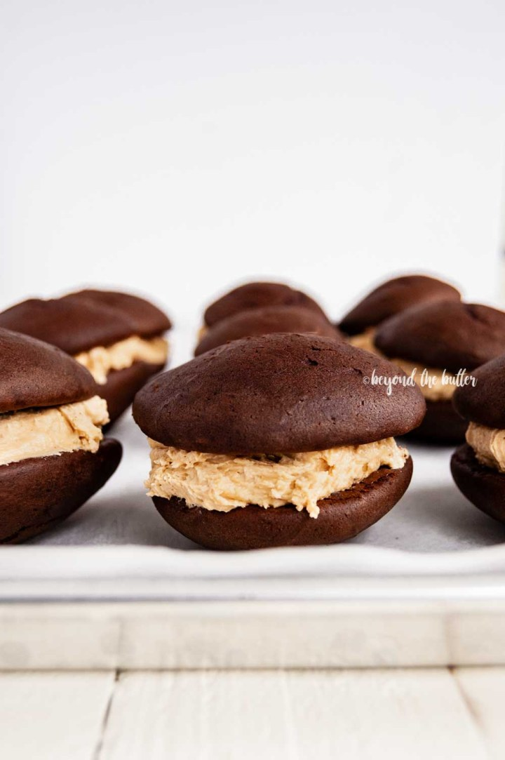 Chocolate Peanut Butter Whoopie Pies on a parchment lined baking sheet | All Images © Beyond the Butter™