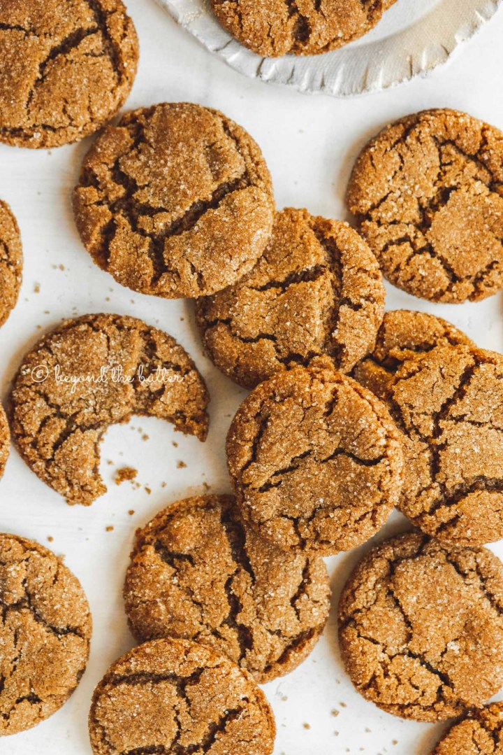 Overhead image of soft and chewy molasses cookies randomly placed on a white background and one half eaten | All Images © Beyond the Butter™