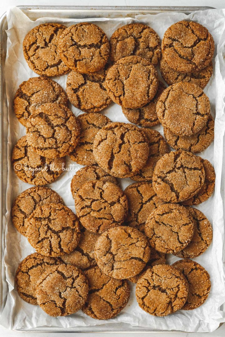 Parchment lined baking sheet topped with super soft molasses cookies | All Images © Beyond the Butter™