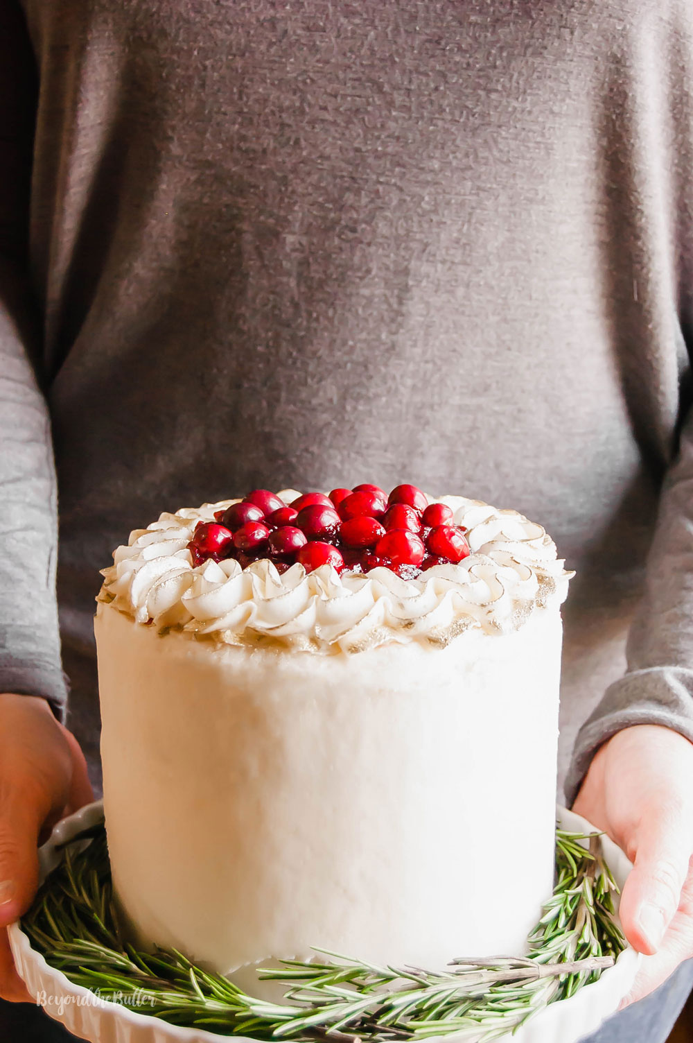 Gingerbread Cake | Person holding Gingerbread Cake with Maple Buttercream Frosting and Cranberry Compote on a cake stand | Image Credit: Beyond the Butter, LLC