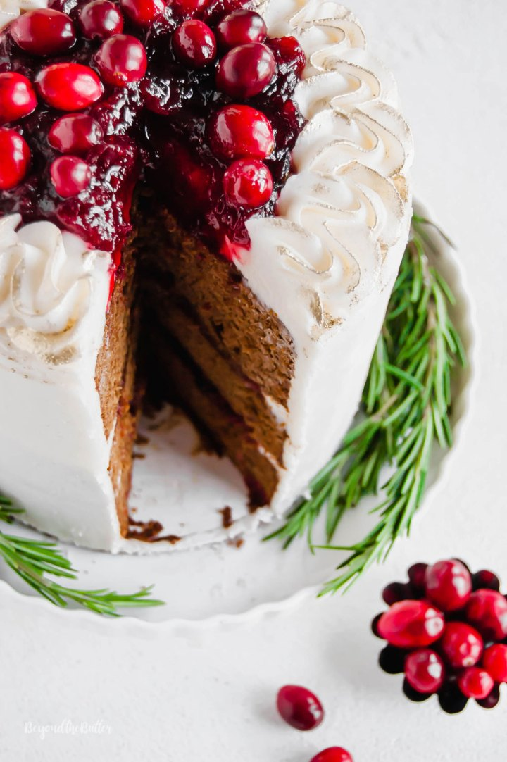 Gingerbread Cake | Angled photo of Gingerbread Cake with Maple Buttercream Frosting and Cranberry Compote with a slice taken out of it and a little bowl of cranberries below it | Image Credit: Beyond the Butter, LLC