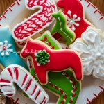 Plate of super soft cut out sugar cookies with royal icing with ornaments and cookie cutters around it | All Images © Beyond the Butter®