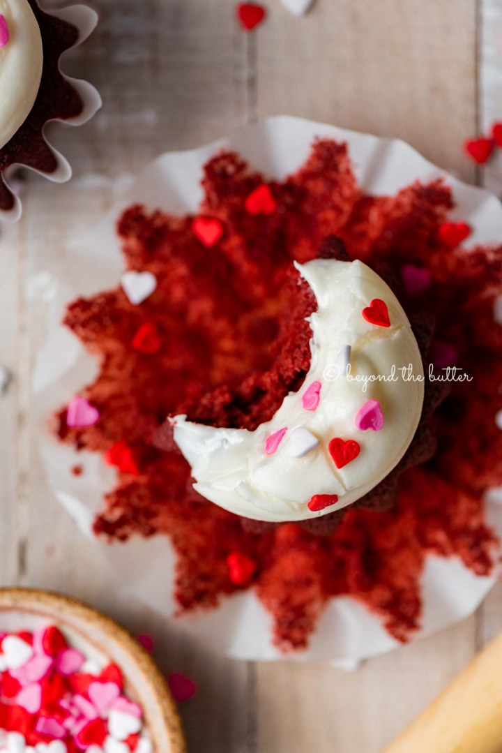 Homemade red velvet cupcakes with one opened and half eaten with a small bowl of Valentine's Day sprinkles on light wood background | All images © Beyond the Butter®