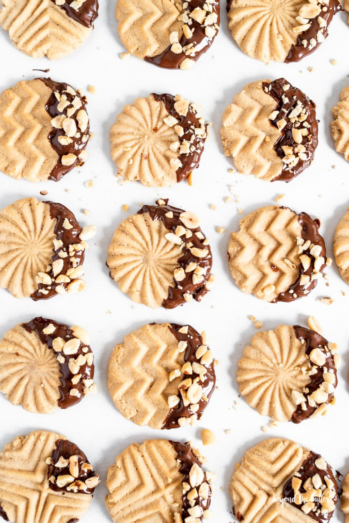 Chocolate Dipped Peanut Butter Cookies   Overhead shot of chocolate dipped peanut butter cookies with chopped peanuts scattered over top   Image and Copyright Policy: © Beyond the Butter, LLC