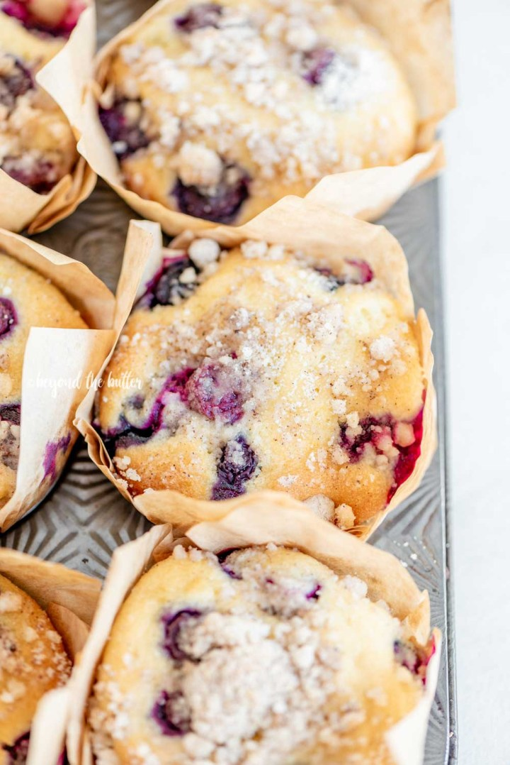 Angled image of lemon blueberry streusel muffins in a muffin tin | All Images © Beyond the Butter™