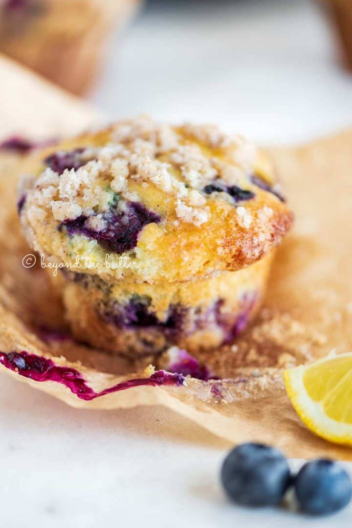 Unwrapped lemon blueberry streusel muffin with lemon wedges and blueberries around it | All images © Beyond the Butter®